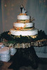 34  This three tier wedding cake has white scrolled icing, green ribbons, raffia and wooden roses on a tree stump.