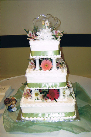 15  This is a three tier cake with celery colored ribbon around each tier. Fresh flowers are arranged between and around the cake top.