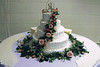 32   This cake has an upscale icing design with fresh roses, greenery and baby's breath bringing a very attractive centerpiece for your reception.