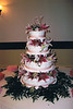 35  This four tier wedding cake has pink ribbons and fresh star gazer lilies.