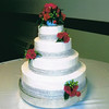 Four tier wedding cake with silver diamonds around each tier, fresh flower nosegays against cake.