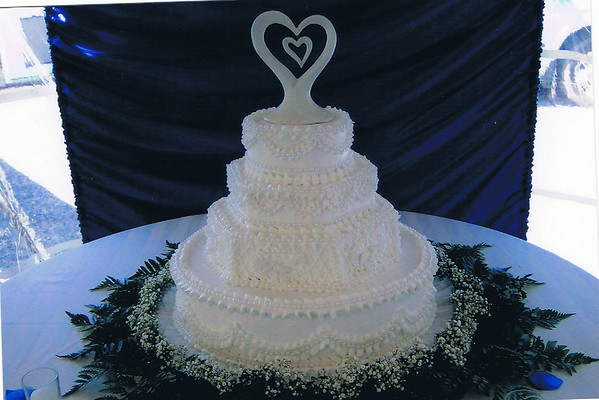 06 This hexagon and round  cake has ruffles and beads with baby's breath and ferns around the bottom.