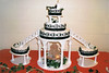 Wedding cake with designs in black and black ribbon on each tier. Silk lilies on cake.