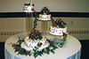 29  This 4 tier cake set on separate pedestals makes a dramatic presence at your reception with the latest colors of brown and red tastefully draped down the sides.