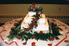 Three tiered  wedding cake with gold ribbon around each tier and fresh red roses.