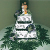 Square tiered cake w/purple ribbon and fresh flowers. Dark purple vines against cake. Cake top was for a firefighter & bride.