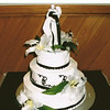 Three tiered round cake with icing scrolls against cake sides in black and white. Black Ribbon around each tier w/ Bride and Grooms name and wedding date printed on. Silk lilies against cake.
