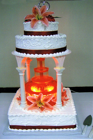 09  This is a three tier cake with icing scrolls on the sides with orange ribbon around each tier. Silk stargazer lilies are arranged around the fountain and cake top.