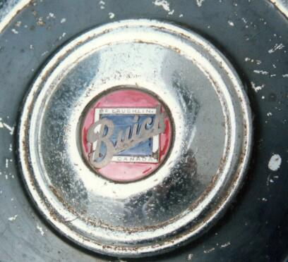 Early Canadian Side-mount hubcap (Close-up on inset enameled medallion)