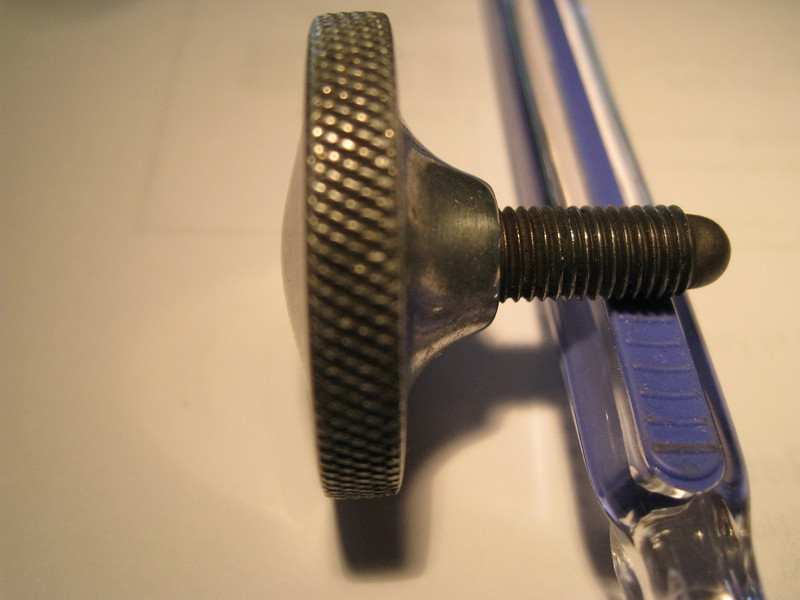 Top knurled nut in windshield stanchion which that controls the swing of the windshield:  (Diam:  1 & 31/64  inches;  Top of dome to underside where screw goes in:  43 / 64  inches;  Thickness at knurled edge:  15 / 64  inches;  Overall length (with screw)  1 & 7/16  inches)
