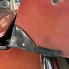 "Corner protector riveted to each of the back hood (bonnet) corners. Leather or rubber - about 2"" on each side.  The rubber hose right in front is a do it yourself protector for the chrome hood strip.  Simply, a piece of hose split and glued to the metal."