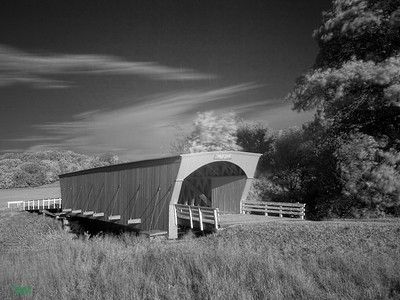 Built in 1884 by Benton Jones, the Hogback Covered Bridge measures 97 feet, and is in its original location in a valley north of Winterset. Hogback gets its name from the limestone ridge which forms the west end of the valley. It was renovated in 1992 at a cost of $118,810. LATITUDE: 41.386480750341185LONGITUDE: -94.04744803905487