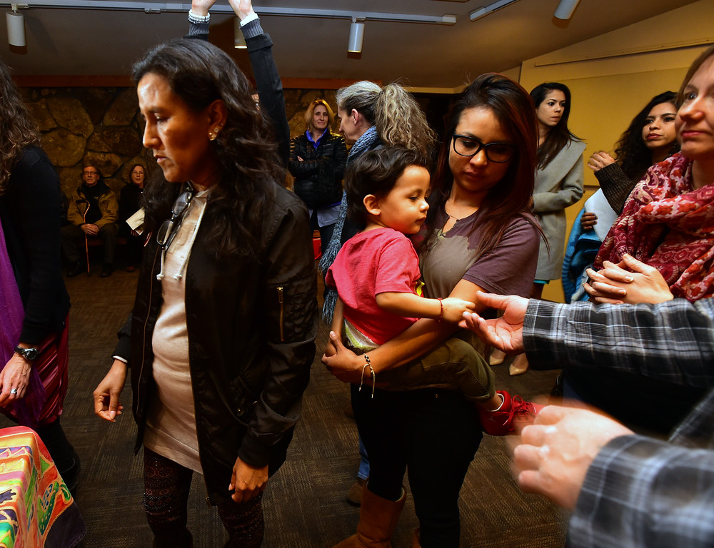 . Someone reaches out to touch the hand of Ingrid Encalada Latorre\'s son Anibal, 2, at a rally in support of the family at the Unitarian Universalist Church of Boulder, where she has been taking sanctuary. Encalada Latorre\'s husband was detained by ICE agents on Thursday. Paul Aiken Staff Photographer Jan 11 2018. .