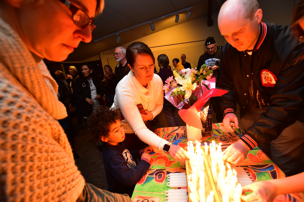 . Meghan McCracken and her son Booker, 4, light candles in support of the Encalada Latorre family at a rally in support of the her at the Unitarian Universalist Church of Boulder, where she has been taking sanctuary. Encalada Latorre\'s husband was detained by ICE agents on Thursday. Paul Aiken Staff Photographer Jan 11 2018. .