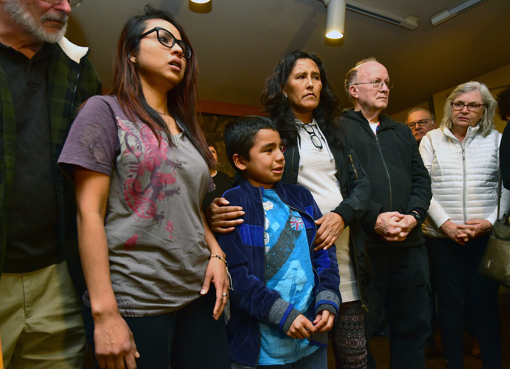 . Ingrid Encalada Latorre, left, listens to her son Bryant, tell the rally at the Unitarian Universalist Church of Boulder how much he misses his father who was detained by ICE agents on Thursday. Holding Bryant\'s shoulder is Jeanette Vizguerra. Paul Aiken Staff Photographer Jan 11 2018.