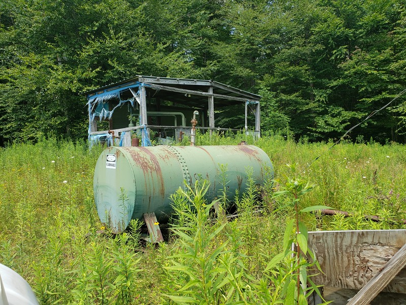 """Electric wires dangling near tank labeled """"Flammable."""""""