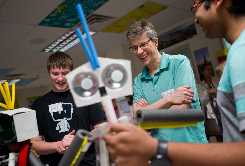 "Student engineers Rhett Sandal (left), from the Innovation Center of SVVSD, and Pranav Iyer (right) from Silver Creek High School, talk with Chris Torrence, a STEM instructor for Summit Middle Charter School, about a low cost robot named Bibli that they helped design in collaboration with Robauto, during Innovate@BVSD at Monarch High School in Louisville on Wednesday. <br /> For more photos go to  <a href=""http://www.dailycamera.com"">http://www.dailycamera.com</a><br /> (Autumn Parry/Staff Photographer)<br /> June 8, 2016"