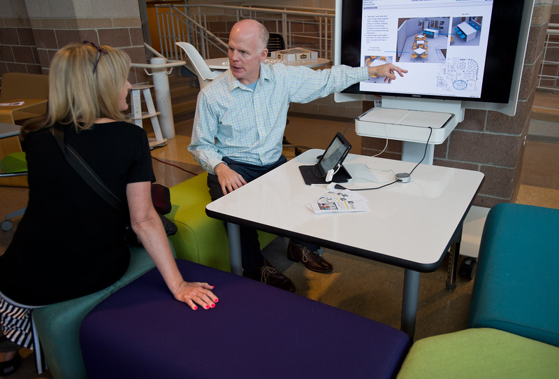 "Eric Bulman, a territory manager with OfficeScapes, shows examples of furniture layouts to Karen Mackie, a librarian at Lafayette Elementary, during Innovate@BVSD at Monarch High School in Louisville on Wednesday. <br /> For more photos go to  <a href=""http://www.dailycamera.com"">http://www.dailycamera.com</a><br /> (Autumn Parry/Staff Photographer)<br /> June 8, 2016"
