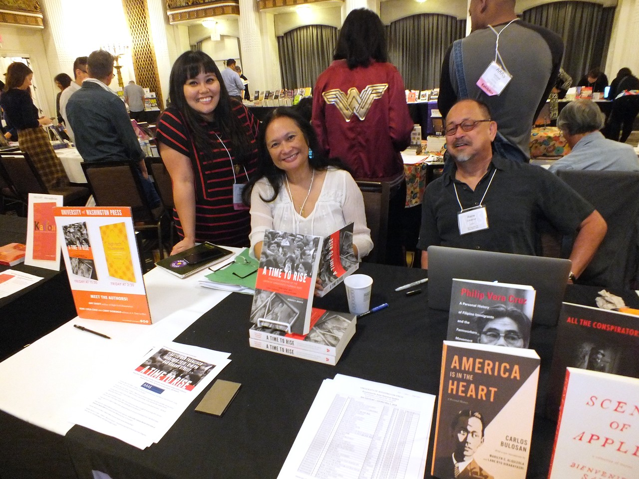 """UCLA Asian American Studies Center Publications Coordinator Barbra Ramos gets her booked signed by co-editors Cindy Domingo and Rene Ciria-Cruz of the KDP Anthology """"A Time to Rise"""" at the University of Washington Publications Table"""