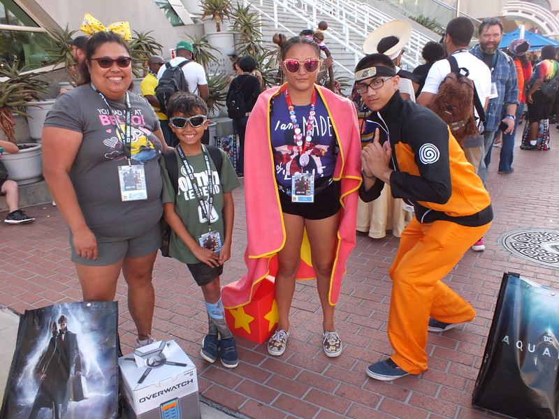 "FilAm attendees (L-R) Paultette Johnson (44) (sporting a Minon shirt), Hayden Johnson (9) (as a Fortnight Character), Bridget Johnson (18)(cos-playing as Garnet from Steven Universe), Ryan MacGilFrey (18) (as Naruto, from Japanese manga), Only Bridget and Ryan have attended before and they ""like the effort that goes into it, like the costumes and (display) stands, it's really good!"" Paulette was excited that she finally was able to get ComiCon tickets after trying for the last 7 years. Next year they plan to really get into the cos-playing"