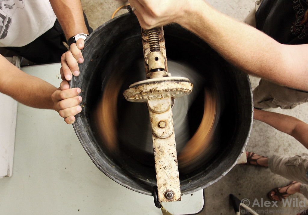 A small, hand-cranked centrifuge extractor spins ripe honey from the combs.