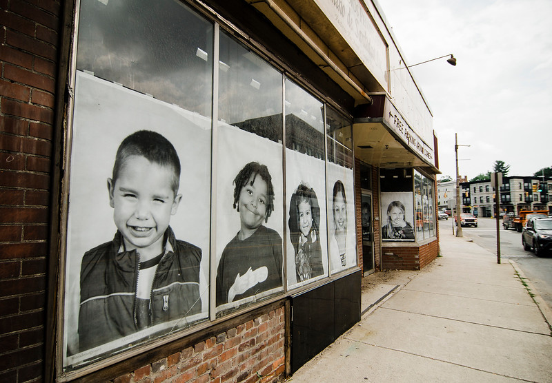 Local artist Coelynn McIninich hangs portraits of North of Main residents and employees in vacant business windows on Wednesday, July 12, 2017. The portraits are part of the Inside Out Project, a large-scale art project that transforms messages of personal identity into pieces of artistic work. SENTINEL & ENTERPRISE / Ashley Green