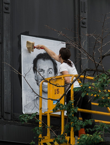 Local artist Coelynn McIninich hangs portraits of North of Main residents and employees in front of Destare on Wednesday, July 12, 2017. The portraits are part of the Inside Out Project, a large-scale art project that transforms messages of personal identity into pieces of artistic work. SENTINEL & ENTERPRISE / Ashley Green
