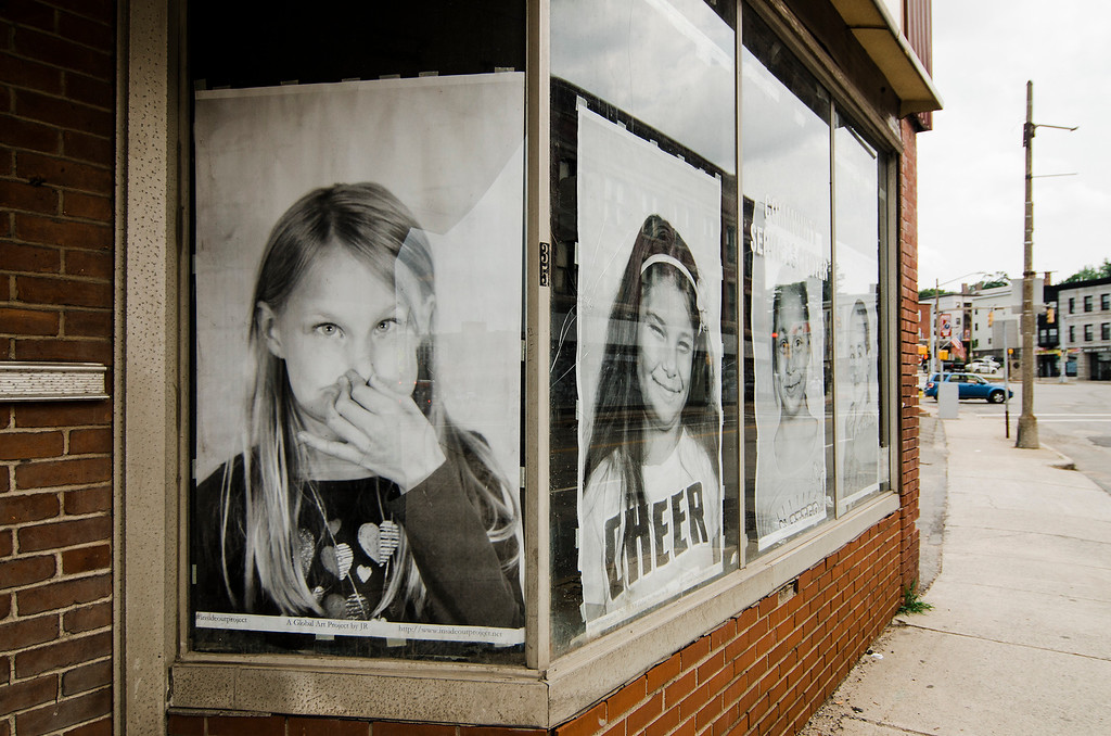 . Local artist Coelynn McIninich hangs portraits of North of Main residents and employees in vacant business windows on Wednesday, July 12, 2017. The portraits are part of the Inside Out Project, a large-scale art project that transforms messages of personal identity into pieces of artistic work. SENTINEL & ENTERPRISE / Ashley Green