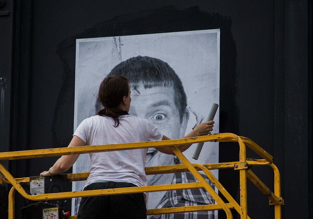 . Local artist Coelynn McIninich hangs portraits of North of Main residents and employees in front of Destare on Wednesday, July 12, 2017. The portraits are part of the Inside Out Project, a large-scale art project that transforms messages of personal identity into pieces of artistic work. SENTINEL & ENTERPRISE / Ashley Green