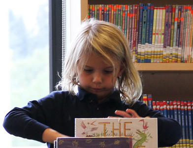A kindergartener explores one of the central book bins to find a story to read on her own.