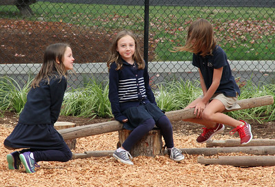 Three friends test out one of the logs as a teeter-totter option.