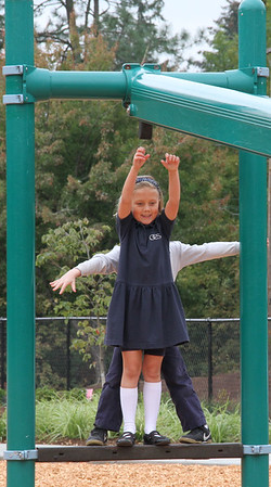 A student excitedly waits for her turn on one of the playground structures.