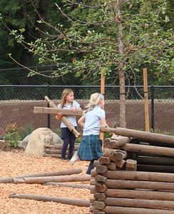 Two girls work together as builders in one of the play area sections.