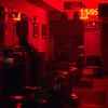 <b>Empty Barber Shop</b> - In the absence of other ambient light, this tiny neon sign makes the empty shop a deep red.