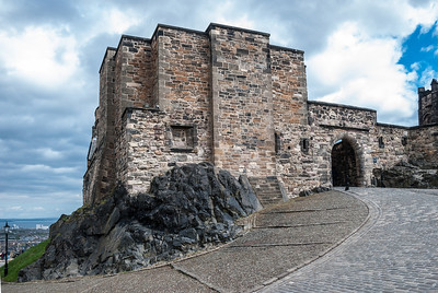Edinburgh Castle  Foog's Gate  Edinburgh Castle is a fortress which dominates the skyline of the city of Edinburgh, Scotland, from its position atop the volcanic Castle Rock.  There has been a royal castle here since at least the reign of David I in the 12th century, and the site continued to be a royal residence until the Union of the Crowns in 1603.