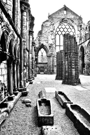 Palace of Holyroodhouse  Ruins of Holyrood Abbey  The ruined Augustinian abbey that is sited in the grounds was founded in 1128 at the order of King David I of Scotland. The name derives either from a legendary vision of the cross witnessed by David I, or from a relic of the True Cross known as the Holy Rood or Black Rood, and which had belonged to Queen Margaret, David's mother.