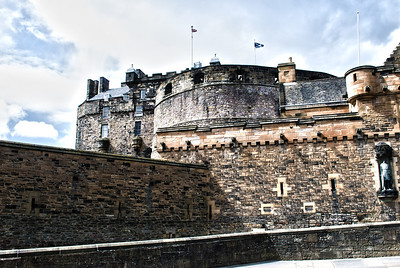 Edinburgh Castle  Edinburgh Castle is a fortress which dominates the skyline of the city of Edinburgh, Scotland, from its position atop the volcanic Castle Rock.  There has been a royal castle here since at least the reign of David I in the 12th century, and the site continued to be a royal residence until the Union of the Crowns in 1603.