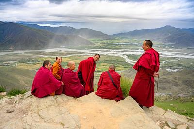 Monks sitting on a rock near Ganden in Tibet