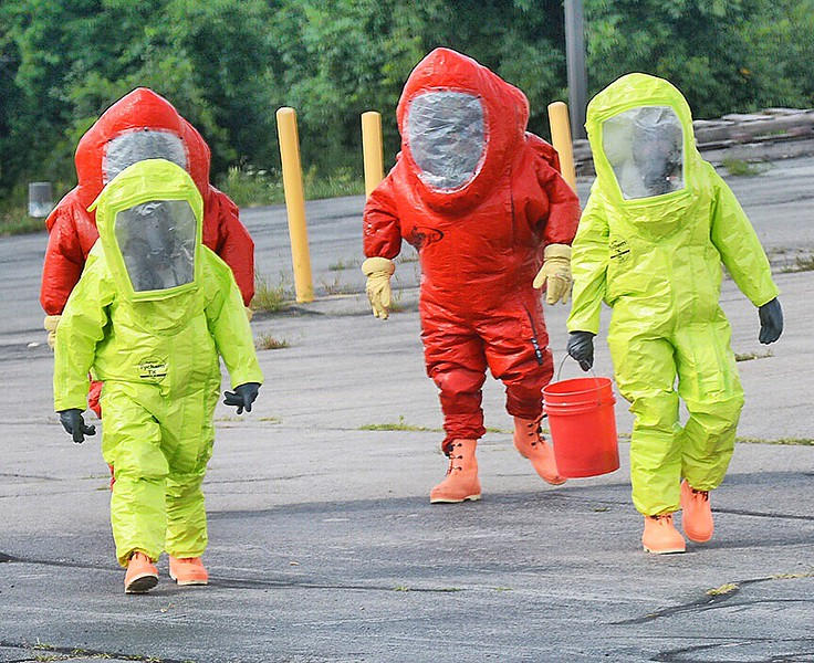 Jack Haley/Messenger Post MediaLocal firefighters in area Haz Mat units exit the building after checking on the condition of the spill.