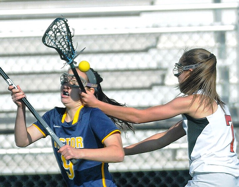 Jack Haley/Messenger Post Media<br /> Victor's Sydney Reed takes a stick to the side of the face from Ilia Bagley  jarring the ball loose as she ran down the sideline.