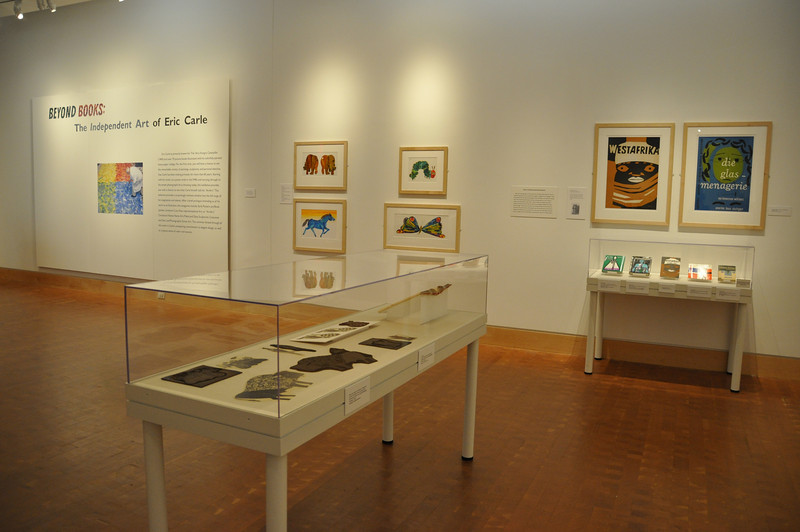 From left to right, wall: Intro Panel, picture book illustrations (facsimile prints), posters and book jackets. Foreground: lino cut & lino print case . [Photo by Kristin Angel for The Eric Carle Museum of Picture Book Art - Reproduction only with permission]