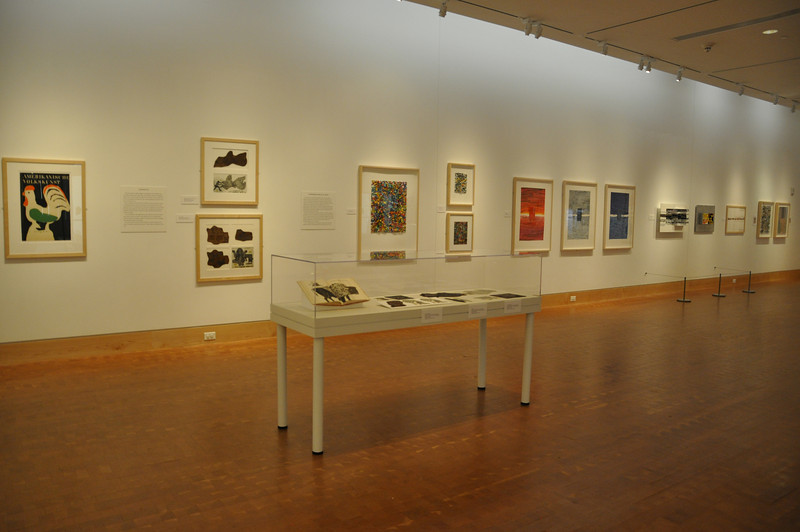 Left to right, wall: final poster, lino cuts and lino prints, non-representational art; foreground: lino cut and lino print case . [Photo by Kristin Angel for The Eric Carle Museum of Picture Book Art - Reproduction only with permission]