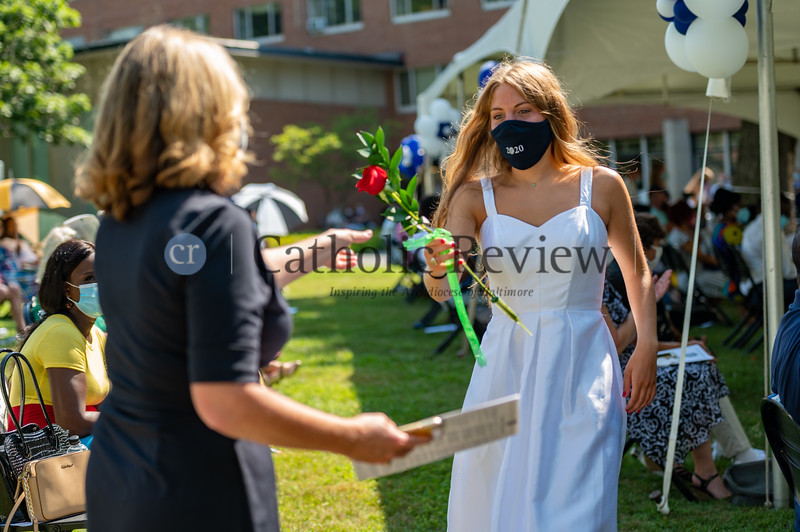 Maria Wellma presents her mother, and IND Class of '88 alum, with a rose during the Institute of Notre Dame's July 26, 2020 graduation ceremonies healed at Notre Dame of Maryland University. (Kevin J. Parks/CR Staff)