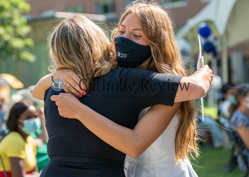 Maria Wellmann hugs her mother, an IND Class of '88 alum, during the Institute of Notre Dame's July 26, 2020 graduation ceremony hosted at Notre Dame of Maryland University. (Kevin J. Parks/CR Staff)