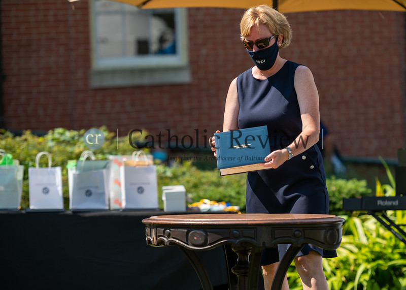 Institute of Notre Dame Head of School, Christine Szala places a diplima on a table belonging to Sister Hildie Sutherland, as part of graduation ceremonies July 26, 2020 at Notre Dame of Maryland University in Baltimore. (Kevin J. Parks/CR Staff)