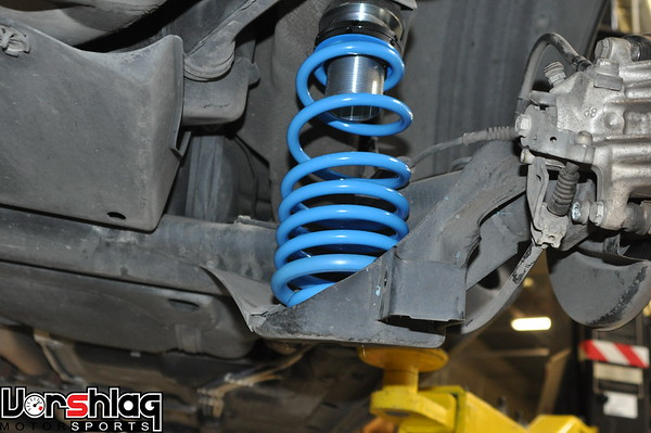 With the shock disconnected it is easy to install the Bilstein progressive rear spring and ride height adjuster. The adjuster goes on the top of the stock spring locating pin, as shown. There is a rubber spacer that goes above the ride height adjuster and a blue friction ring that goes between the spring and ride height adjuster.