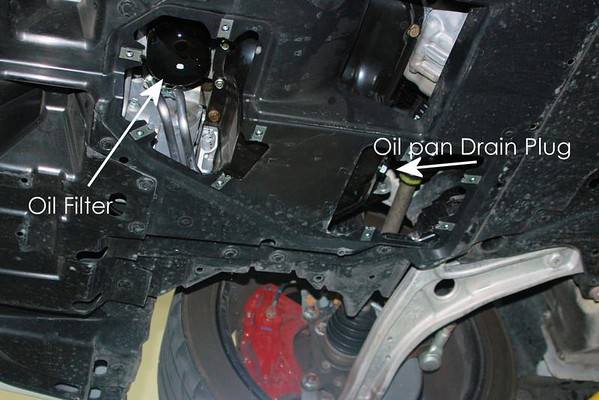 With the inspection cover removed you can now see the oil filter and oil pan drain plug. There are several other drain plugs (center diff, transaxle) - don't remove those!<br /> <br /> Getting the oil filter off can be a chore - I used the proper filter wrench and still had to fight with it for a bit, and lost some skin. The inspection cover hole could be larger and make this job a lot easier. I found that by sticking the wrench on the filter in the main hole and snaking my arm through the oil pan hole gave enough leverage to get it off. The original filter was put on by a gorilla.
