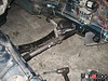 """To install the LS1 V8 it helps greatly to lower the K-member, as shown in this picture. There are 4 bolts that connect the K-member to the chassis, and they are either loosened greatly or removed completely (the struts will keep the K-member from falling away completely). This extra """"head room"""" will allow the rear sump of the LS1 engine clear the K-member."""
