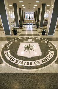 "The seal of the CIA, Central Intelligence Agency located in Langley / McLean Virginia.  In the lobby is the seal of the agency on the floor with the statue of ""Wild Bill"" Donovan, who brought the agency from the day of the OSS (Office of Strategic Services) during World War II into todays CIA.  On one side of the lobby  wall is marked by stars, one for each operative that has given his life in the line of duty.  A book notes the names the stars represent, but some remain blank, operatives whose names and heroic actions remain secret."