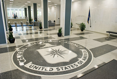The old entrance of the Central Intelligence Agency Headquarters displaying the seal of the CIA on the floor. In the background (right) is the Memorial Wall which currently has 102  stars engraved for each member of the agency that gave of his/her life in the line of duty.  Names of those are listed in the book below, with a 37 not being listed and will remain Secret for the nature of the work they were doing.  Photo: Greg E. Mathieson Sr. / MAI